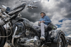 Elderly man smiles broadly as he sits on the back of a powerful three-wheeled motorcycle